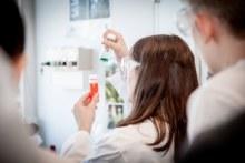 Experimentierlaune: Reagenzgläser mit roter und grüner Flüssigkeit werden hochgehalten (Foto: Femtec.GmbH)
